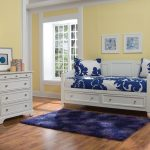 white wooden daybeds with storage with white and navy white bedding linen plus blue rug and wooden floor plus white dresser and soft yellow painted wall
