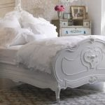 A fancy white bed furniture in pretty classic style and with white bedding white pillows and white comforter