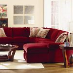 Beautiful red microfiber sectional with modern cased throw pillows round wood framed glass coffee table with wood base round glass side table with wood frame white area rug