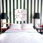 Bed without headboard with monochormatic strip wallpaper and white frameless wall art with colorful polka dots patterns a pair of table lamps with white base and black lampshade