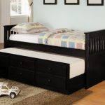 Black painted wooden double trundle with drawers and headboard white mattress brown wool bedroom rug