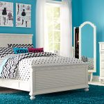 Blue wall paint color white bed frame with white textured headboard monochromatic bedding idea with polka dot patterns white bedside table with drawers white bedroom vanity with mirror free