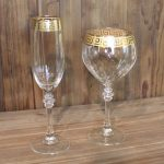 Boxwood Gold Greek Key Rimmed Wine Glasses And Champagne Flutes With A Greek Key Design And Various Shaped Placed On Wooden Table