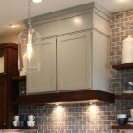 Burrows Cabinets And Wood Vent Hood With Unique Light Fixtrues And Stone Wall