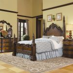 Fancy bed frame with classic styled headboard and footboard dark brown painted wood bedside table with drawers a bedroom vanity with dark brown wood framed mirror