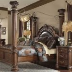 Fancy bedroom set in rustic style with bed frame which has four wood pillars dark brown coated wood bedside table a classic table lamp