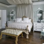 Fancy bedroom set with classic bed frame with curved classic headboard comfy white bedding and pillows classic settee furniture clsssic white bedroom vanity with white framed mirror a corner chair