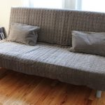 Folded chair with futon and pillows in grey color as guest bed