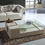 Frameless transparent glass top center table with smaller wood top addition on left brown shaggy rug for modern living room a white sofa with accent pillows
