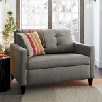 Grey Twin Size Sleeper Sofa With Striped Pillow Next To Round Side Table
