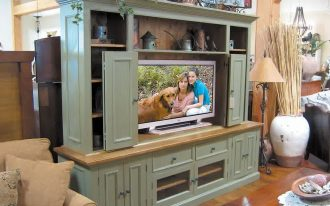 Grey painted wood entertainment center with sliding door base storage and shelving units