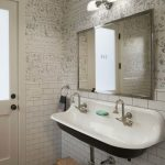Kohler sink for bathroom with two water faucets and nickel framed mirror