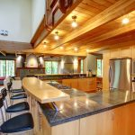 L-shaped-kitchen-island-with-two-tiered-and-modern-rustic-look-and-open-plan-design-in-rich-natural-wood-tones-and-large-granite-countertop