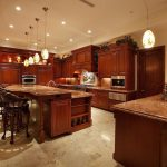 Large-two-tier-kitchen-island-with-marble-countertop-and-dining-seating-and-built-in-storagewith-rich-red-wood-over-beige-marble-flooring-source-from-Zillow-DigsTM