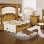 Luxurious fancy bed set idea with extra sized bed frame in gold tone a pair of bedside tables with table lamps a settee furniture a bedroom vanity with mirror and vanity chair a bedroom rug
