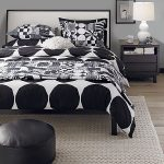 Mid century modern bedding idea in monochrome round black ottoman textured white bedroom rug black painted wood bedside table with bookshelf and drawers modern table lamp in white