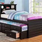 Modern trundle beds made of wood in dark finish and decorative rug plus headboard with storage