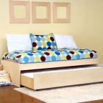 Modern trundle beds with light finish plus polka blue bed sheet together with cozy rug and wooden floor plus wooden frame on wall decoration