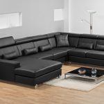 Most comfortable black leather sectional sofa with chaise and low coffee table plus small rug at the center of living room plus glass top end table