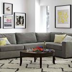 Most comfortable sectional sofa in grey scheme with round wooden coffee table and paterned rug plus artistic pictures on wall decoration