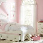 Pink themed bedroom decorating idea with single bed frame and white headboard plus storage mini white lace bed drapery a white storage system an oval mirror with white frame a bedside table
