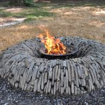 Round outdoor fire pit design with piles of stone