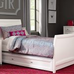 Simple white bed frame with semi curly headboard and footboard white bedroom vanity with white framed mirror white bedside table with drawers a table lamp with blue body and white lampshade