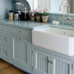 Single white and deep farm sink with glossy nickel water faucet light blue countertop light blue wood base kitchen cabinets