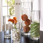 Three ideas of transparent glass vases which contain white natural stones leaves and flowers