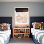 Twin bed frames with tall headboards a bookshelf as the bedside table