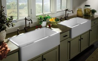 Two units of white farm sinks for kitchen with black wrought iron water faucets