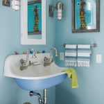 Wall mounted kohler sink with two faucets white framed mirror a pair of vanity light fixtures