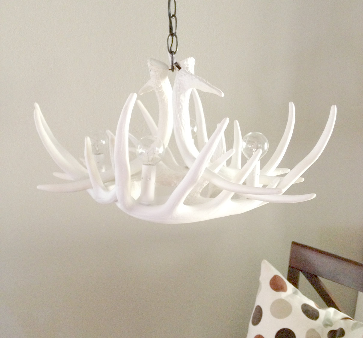 White antler chandelier homesfeed white antler chandelier above wooden chair mozeypictures Image collections