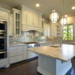 White Kitchen With Marble Kithen Island And Wood Vent Hood
