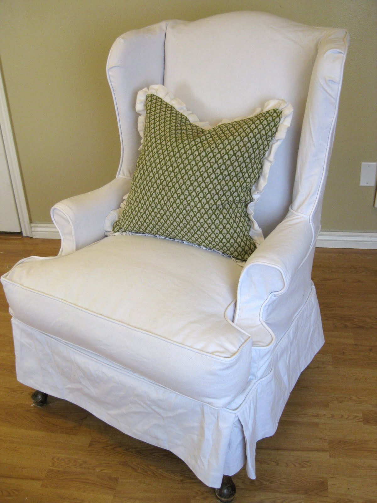 White Slip Cover For Chair In Wingback Design And Green Pillow
