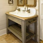 White kohler sink with gold tone water faucet and wooden sink stand two mirrors with cool frames