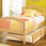 Wooden double trundle bed design with cozy bedding and yellow and pink bedcover