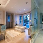 Adorable And Luxurious Bathroom Mansion Deisgn With Walk In Shower And White Bathtub And Curved Bay Window And Wooden Floor