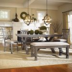 adorable countryside style dining room with gray table and bench and chairs and white rug and wooden floor and chandelier