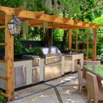 adorable furnished wooden pergola for outdoor tropical kitchen layout design with modern cabinetry and kitchen set and dining table with lantern