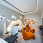 adorable interior design of apartment with orange chair and tv console and unique window shapes and white desk
