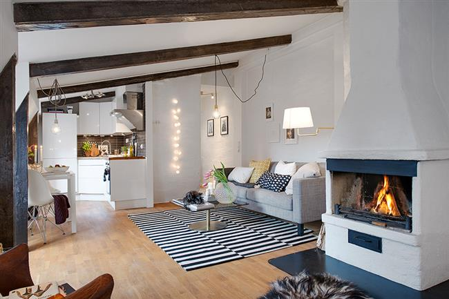 adorable loft home design idea with fireplace stripe area rug and gray sofa and wooden floor and esposed rustic beams on the ceiling