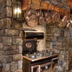 adorable rustic kitchen in country home design with stainless steel cook top and wooden wall rack and stone wall