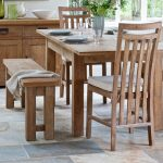 adorable rustic wooden dining table with tall backrested white chair and wooden bench on stone floor