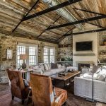 all rustic interior design in stone house with wall racks and white sofa and caramel rone wing chairs and wooden floor and open plan