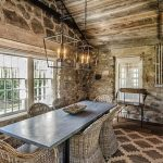 amazing interior design of stone house with rustic wooden ceiling and stone wall and area rug and wooden floor and rattan chairs