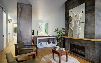 amazing interior design with gray concrete siding accent and fireplace with wooden rack and wooden floor and wooden small coffee table and green arm chairs