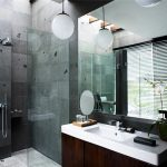 amazing modern bath with walk in shower and wooden cabinet vanity with white top and frameless wall mirror and pendants