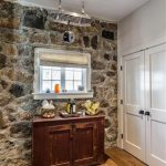 amazing stone house interior design with white wooden door and stone sidewall and wooden antique hallway storage