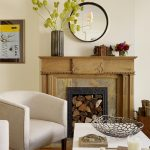 appealing family room with elegant and rustic mantel decor beautified with vase and round mirror together with white armchairs and stylish coffe table